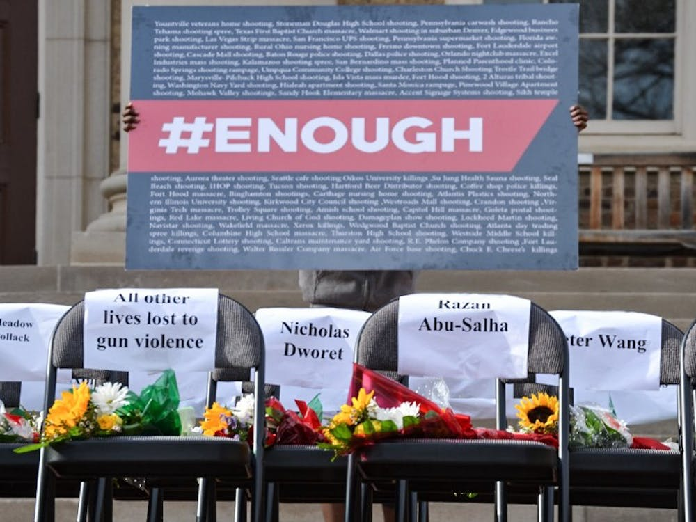 The #Enough sign includes the names of the recent shootings in America.