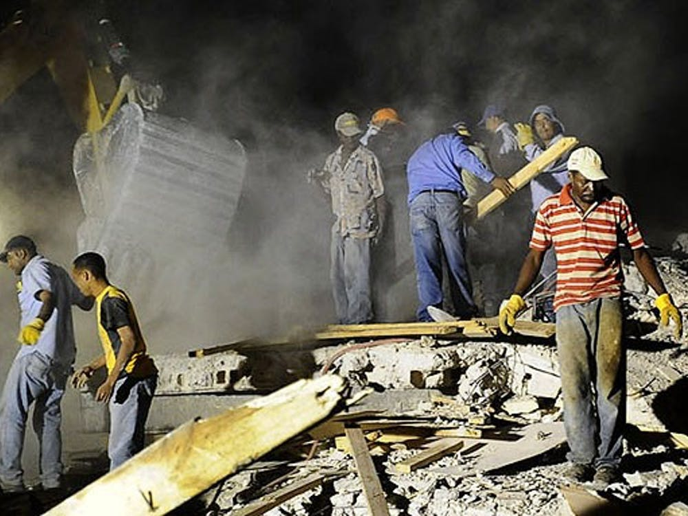 Haitians work to rescue man who is trapped in the rubble in Port-au-Prince. Illustrates HAITI (category i), (c) 2010, The Washington Post. Moved Thursday, Jan. 14, 2010. (MUST CREDIT: Washington Post photo by Carol Guzy.)