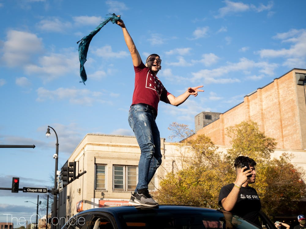 A person waves a scarf atop a car driving by CCB Plaza.