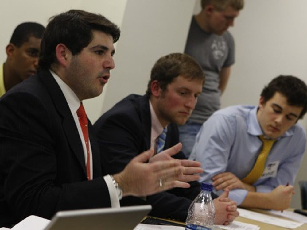 Interfraternity Council President Eric Kaufman (left) and other fraternity members voice their concerns about the RGAC process Wednesday night in front of administrators and representatives from RGAC and Campus Council.
