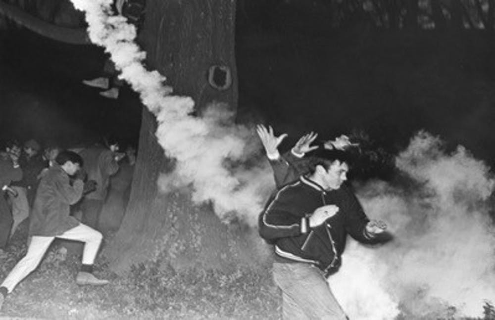 Tear gas scatters the onlookers and supporters outside of Allen Building. Courtesy of Durham Civil Rights Heritage Project (The Herald Sun).