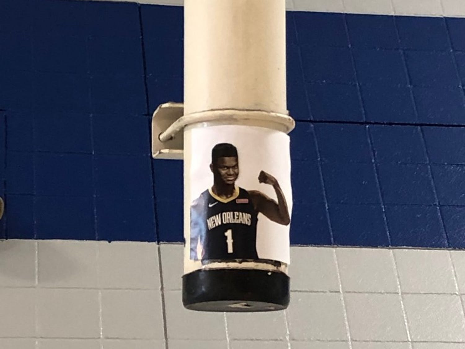 The image of a smirking Williamson ensures nobody will ever forget why pickup games on the first floor of Brodie Recreation Center are now limited to one full court