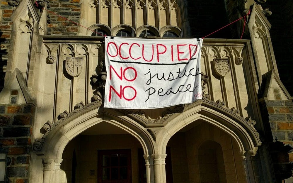 <p>Students sitting in the Allen Building in protest revealed the banner above Saturday afternoon.</p>