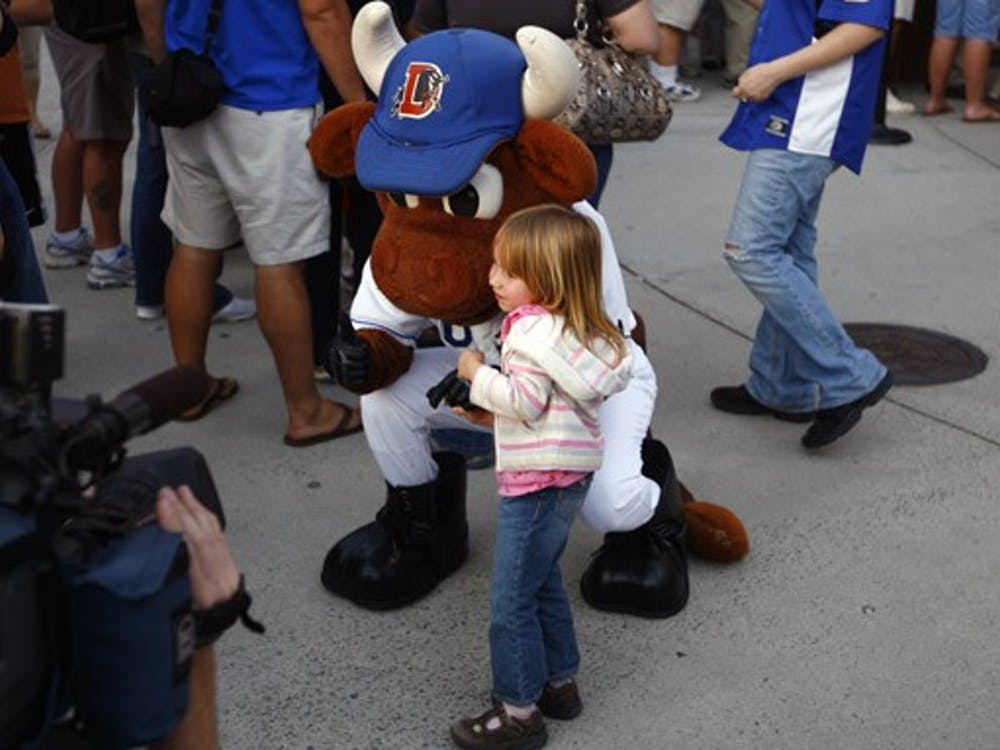 The Durham Bull's mascot poses with a fan during the team's celebration of its recent national championship Wednesday night. The event featured free hot dogs and games of catch inside the Durham Bulls Athletic Park.
