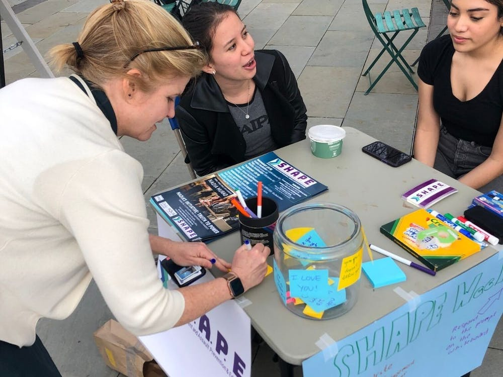 Mary Pat McMahon, vice provost/vice president for student affairs, at a SHAPE week table with two students.