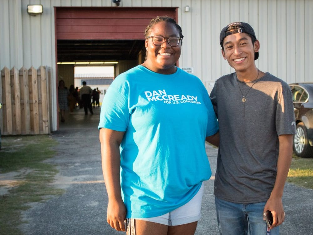 Peace Ajirotutu, left, and Brian Flores have volunteered with McCready's campaign and attended the Lumberton rally.