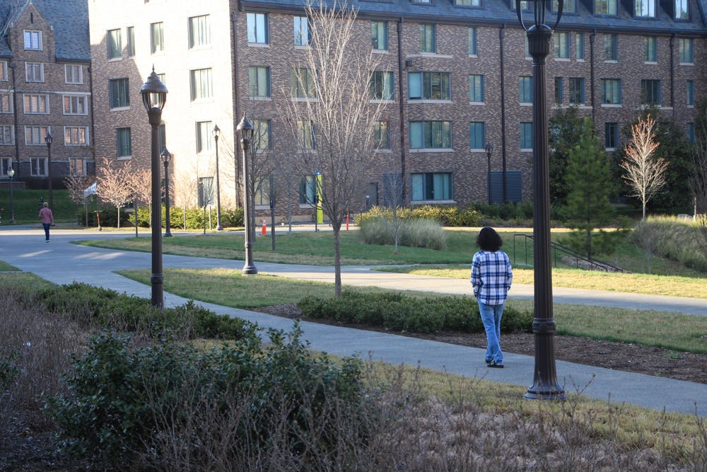 <p>A student walks alone on campus during Duke's stay-in-place order.</p>