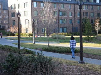 A student walks alone on campus during Duke's stay-in-place order.