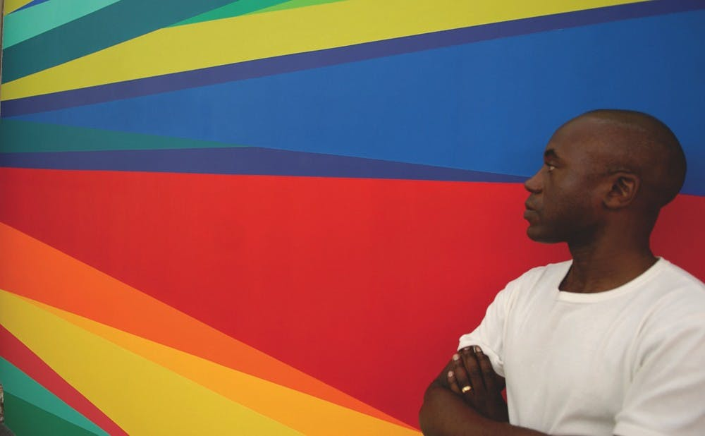 <p>Artist Odili Donald Odita poses with a mural he designed. Odita designed two commemorative murals in the Nasher and the Downtown Durham YMCA in honor of the museum's 10th anniversary. </p>