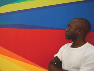 Artist Odili Donald Odita poses with a mural he designed. Odita designed two commemorative murals in the Nasher and the Downtown Durham YMCA in honor of the museum's 10th anniversary.