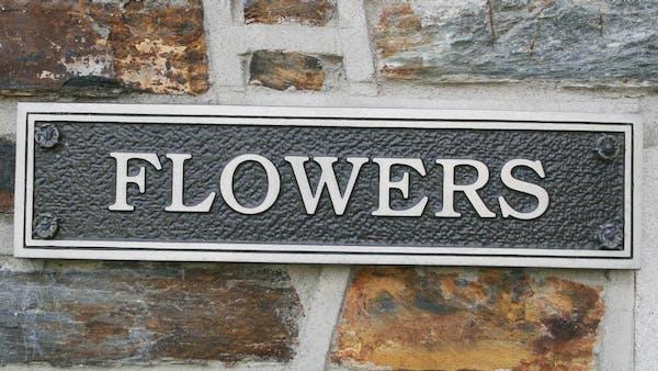 Closeup of the Flowers Street nameplate