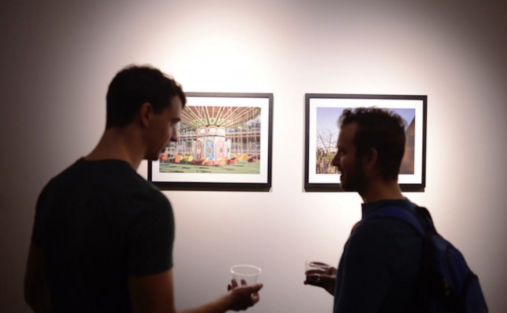 "Two visitors chat at the opening reception for ""Looking North"" last Friday."