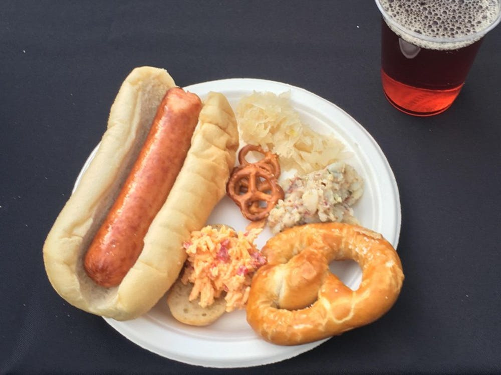 A plate with Polish sausage, sauerkraut, Obazda and pretzels.