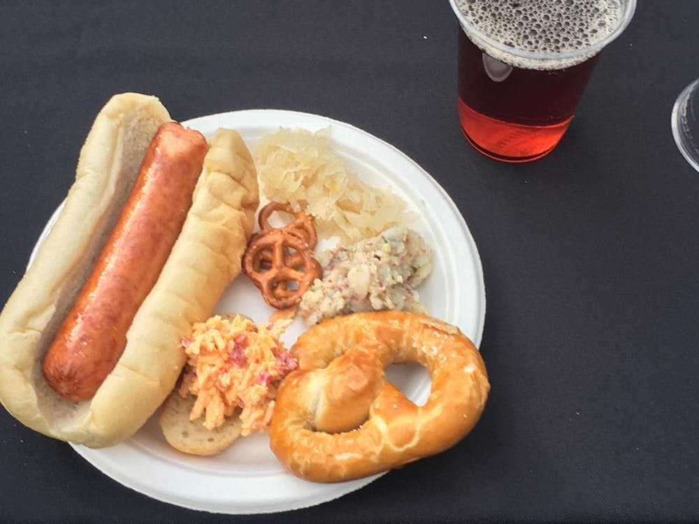 A plate with Polish sausage, sauerkraut, Obazda and pretzels.