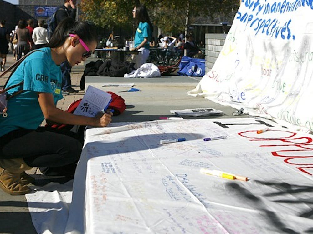 A student expresses her opinions on the merger of the Multicultural Center and the International House on a large white sheet Monday afternoon.