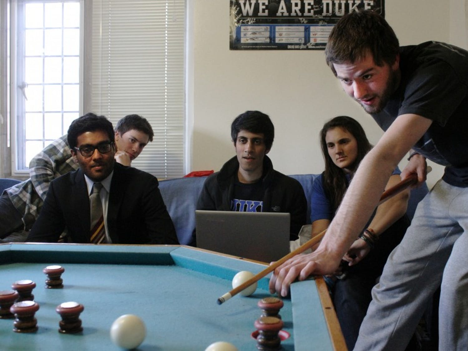 Tyler Glass shoots a bumper pool ball in his dorm room as spectators look on.