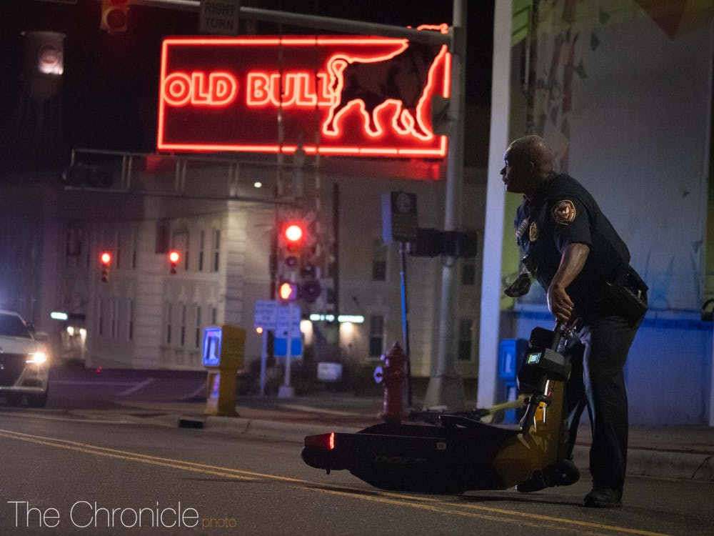 A police officer clears an electric scooter blocking the roadway left behind by protesters.