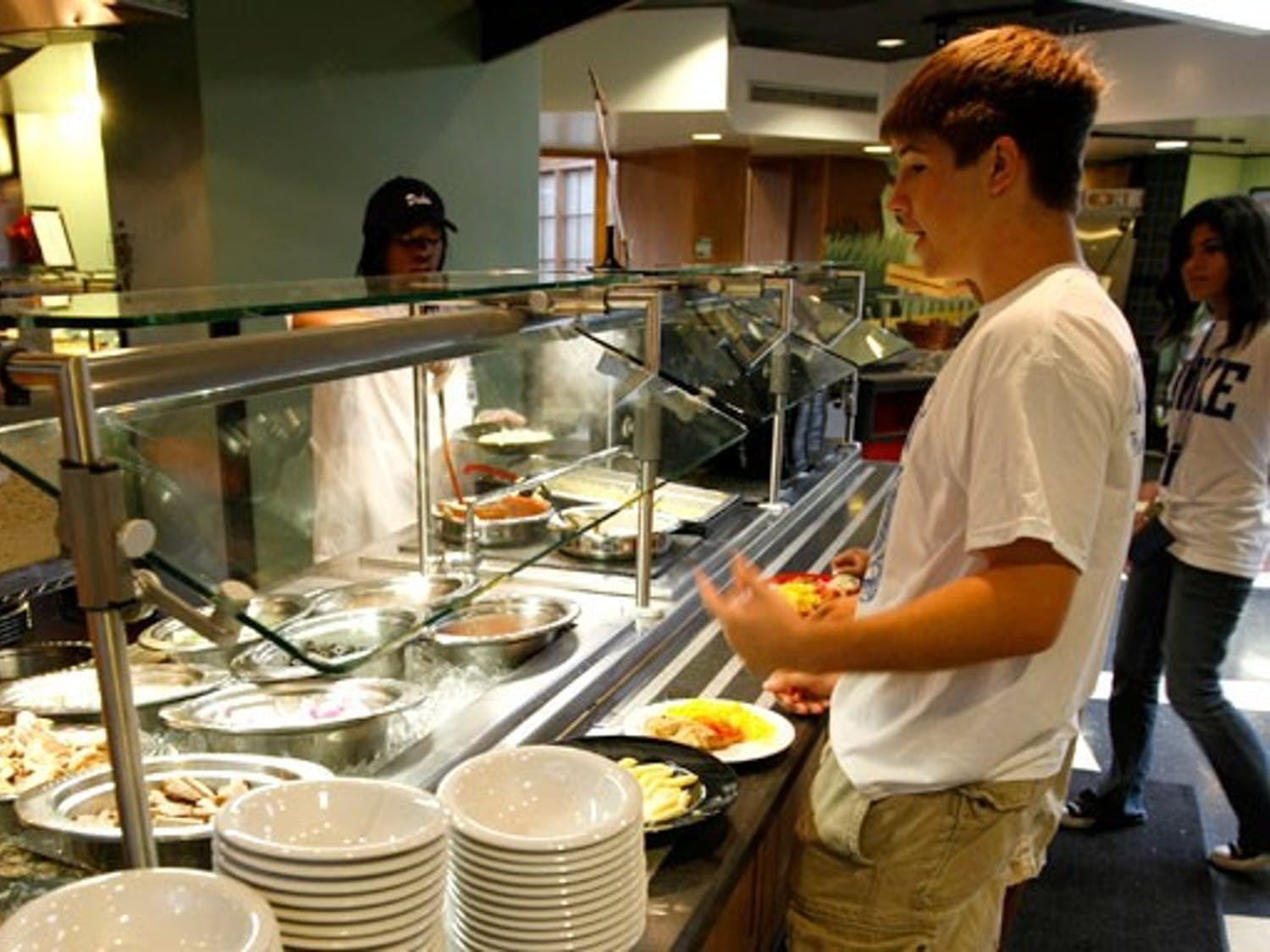 A student is served food at the Marketplace.  Administrators and students recently rejected a proposed first-year dining plan that would have increased the number of Marketplace meals included per week.