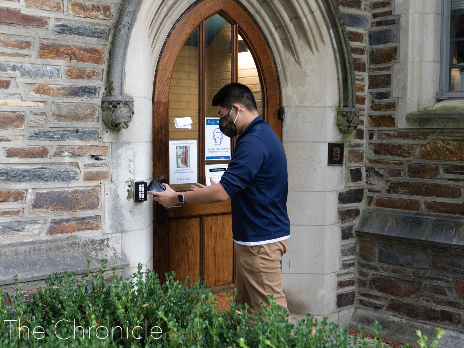 A student swipes in to a West Campus dorm.