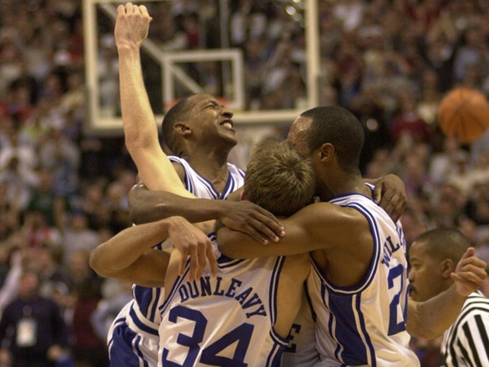 Chris Duhon, Mike Dunleavy, Jay Williams and one unidentified player celebrate after Duke's victory in the 2001 national championship game.