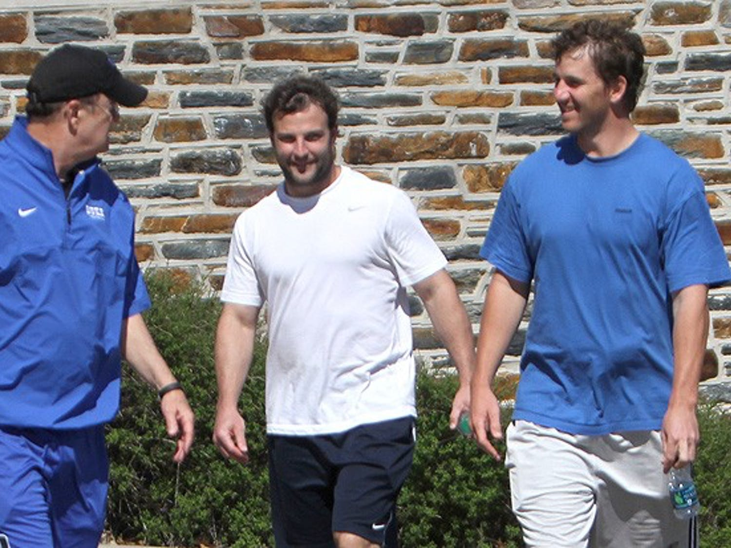 NFL stars Eli Manning and Wes Welker walk with Duke head coach David Cutcliffe outside the Yoh Football Center. Peyton Manning was close behind.