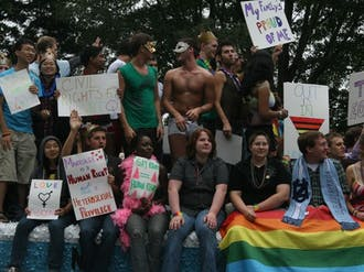 Students ride along in the 25th annual North Carolina Pride Festival and Parade off East Campus Saturday.