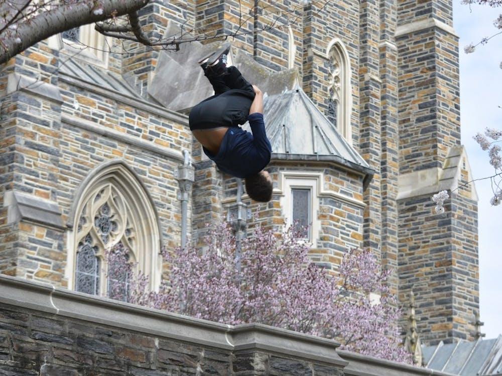 Senior David Ivey flips off a wall near the Duke chapel.