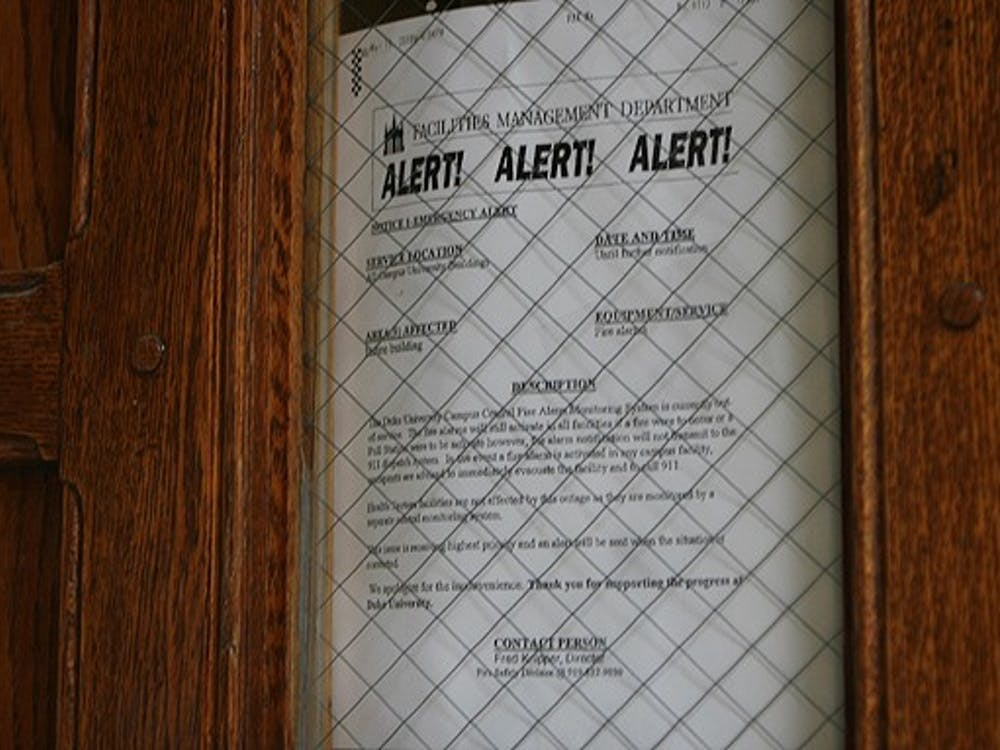 Signs posted Friday at entrances to dormitories across East and West Campus warn students that the fire alarms will not automatically notify Police in case of a fire.
