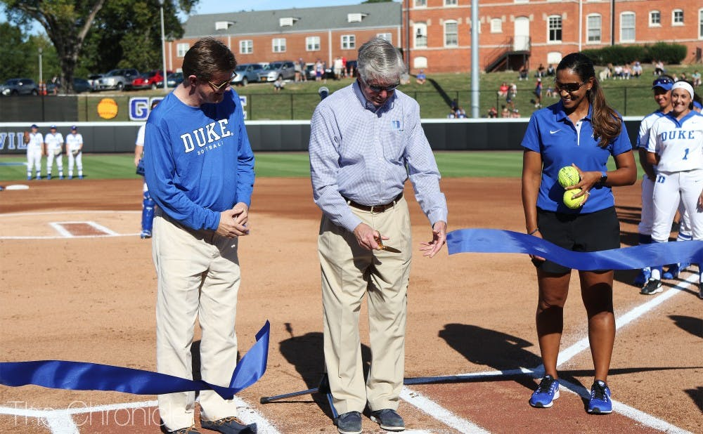 <p>Duke President Vincent Price, vice president and director of athletics Kevin White and head softball coach Marissa Young cut a ribbon to open Saturday's landmark game.</p>