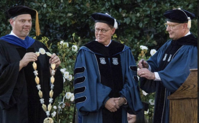 Vincent Price, center, just wrapped up his first year in office. in this photo, Board Chair Jack Bovender, right, and Academic Council Chair Don Taylor, left, place the presidential regalia on Price at his inauguration.