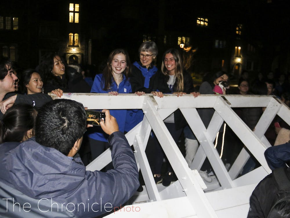Dean of Students Sue Wasiolek poses for photo with students atop the bench.