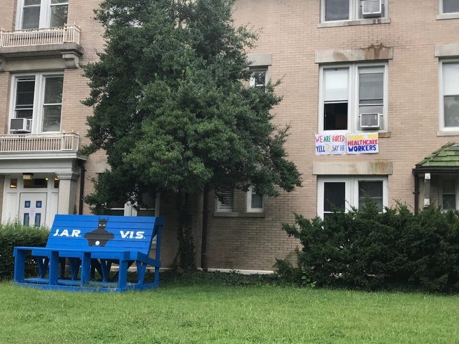 """A poster hanging from a window hints at Jarvis dorm's purpose as an isolation space, reading, """"We are bored. Yell up to say hi."""""""