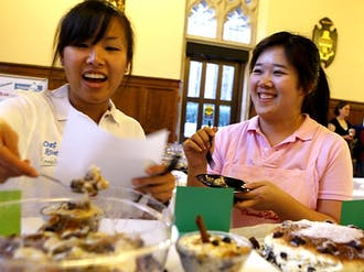 Two restaurateurs from Grand Asia Market, who served as judges, enjoy sweets served at the Dessert Expo in the Great Hall Monday evening. The event, hosted by the Culinary Society, received positive reviews from attendees.