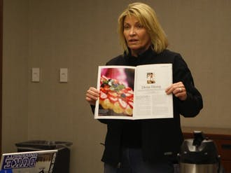 """Refectory owner Laura Hall presents a write up of the Refectory from a September issue of """"Our State"""" magazine at Monday's Duke University Student Dining Advisory Committee meeting."""