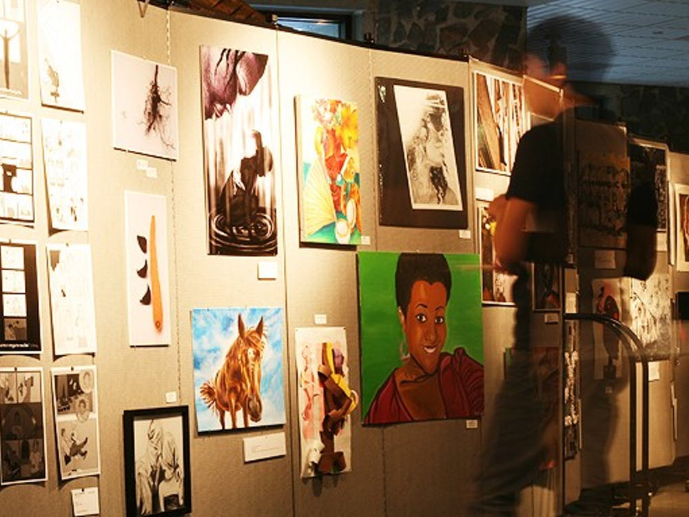 A student gazes at the student art on display in the Bryan Center during the inaugural Duke Arts Weekend, which featured art work from alumni, as well as undergraduate and professional students.