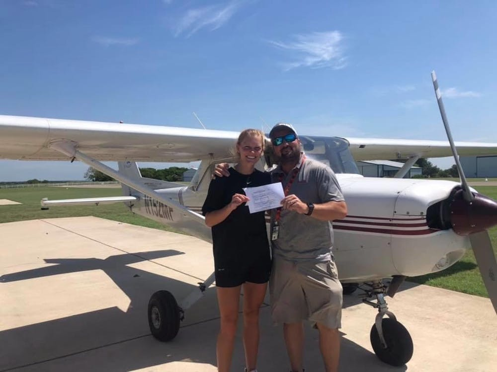 Sydney Simmons standing with her FAA examiner, holding her new private pilot certificate.