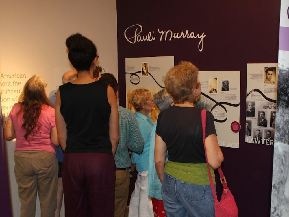 Visitors to the Pauli Murray exhibit analyze the works on display at the Scrap Exchange.