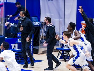 Duke's sideline celebrates after Virginia's last-second shot attempt falls short at the buzzer.