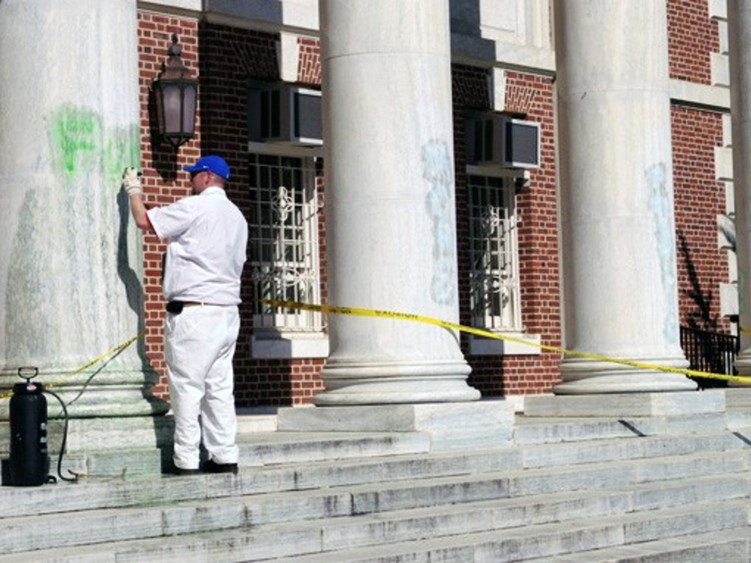 A University staff member cleans up graffiti painted Saturday on the columns of Lilly Library on East Campus. Wilson Residence Hall was similarly vandalized.