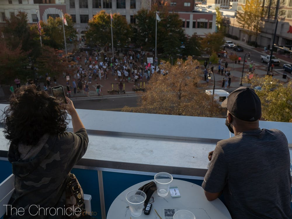 Patrons of the Patio at the Unscripted Hotel in Durham watch the celebration down below in CCB Plaza.