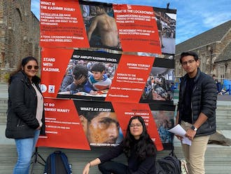 """Students in front of a poster on the BC plaza at the """"Unpacking the Occupation of Kashmir"""" awareness event."""