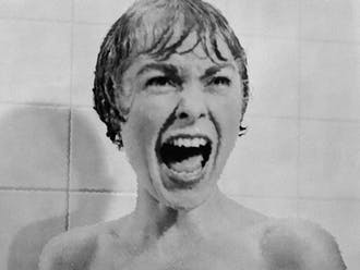 Marion Crane screams in terror as Norman Bates rips open her shower curtain.