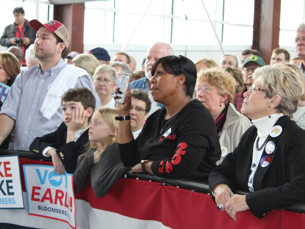 A woman, pictured second from the right in the front row, interrupted Bloomberg's speech with a question Thursday afternoon.