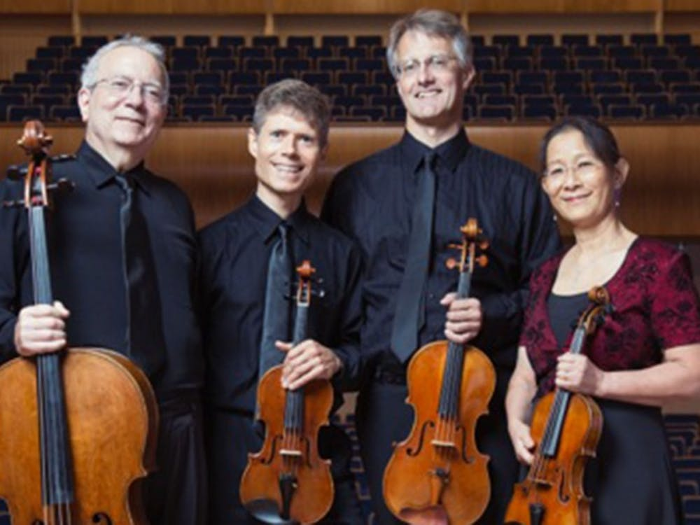 The Ciompi Quartet­—comprised of Eric Pritchard, Hsiao-mei Ku, Jonathan Bagg and Fred Raimi—smiles with their instruments, two violins, a viola and cello.