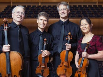 The Ciompi Quartet—comprised of Eric Pritchard, Hsiao-mei Ku, Jonathan Bagg and Fred Raimi—smiles with their instruments, two violins, a viola and cello.