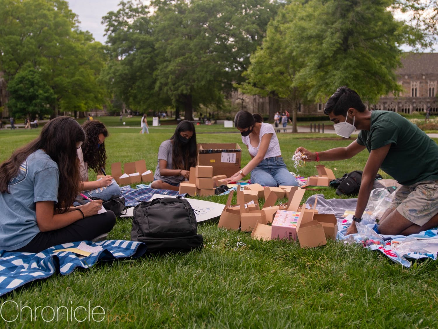 """Campus students decided to use their beautiful spring days to make care packages together for Duke students to use during finals. """"While we made these packages to help others feel cared for, I found the act of making the packages in the sun on the quad therapeutic in and of itself. I haven't been able to feel this way for a while, especially with the spring I lost last year,"""" said Hindu Students Association co-president Sarabesh Natarajan."""