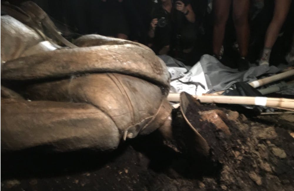 <p>The Silent Sam Statue was topped by protesters Monday night. This is the statue a few minutes after it was overturned. | Courtesy of Mike Ogle</p>