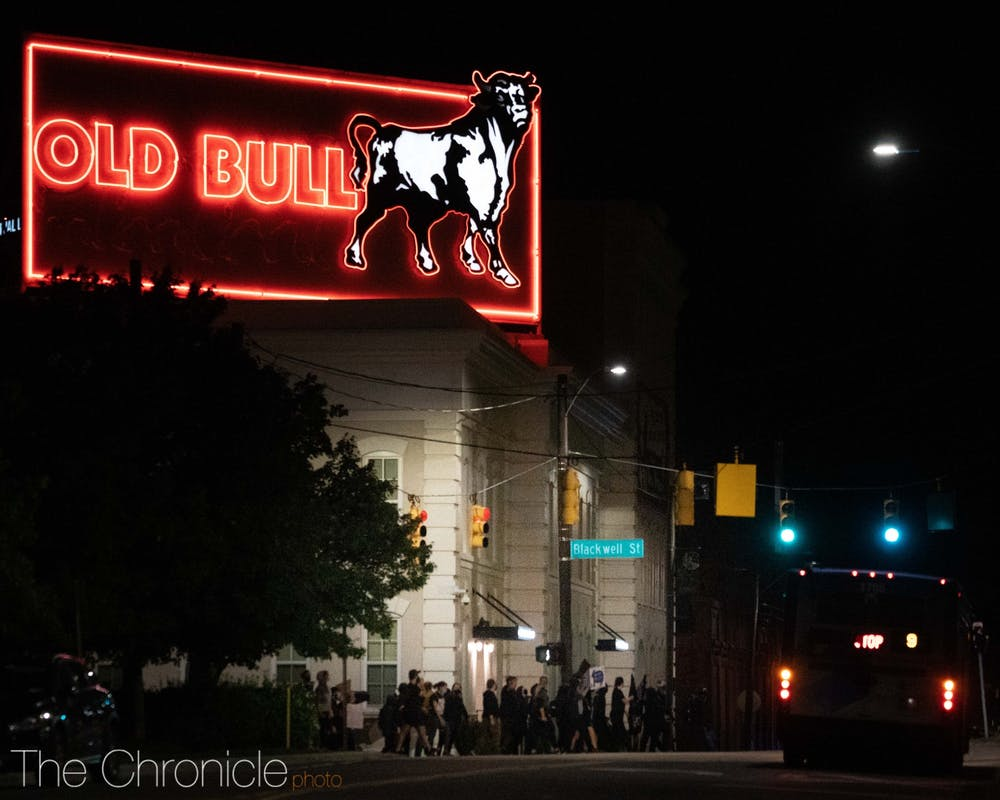 <p>Protesters march past the Old Bull sign on Wednesday night.&nbsp;</p>