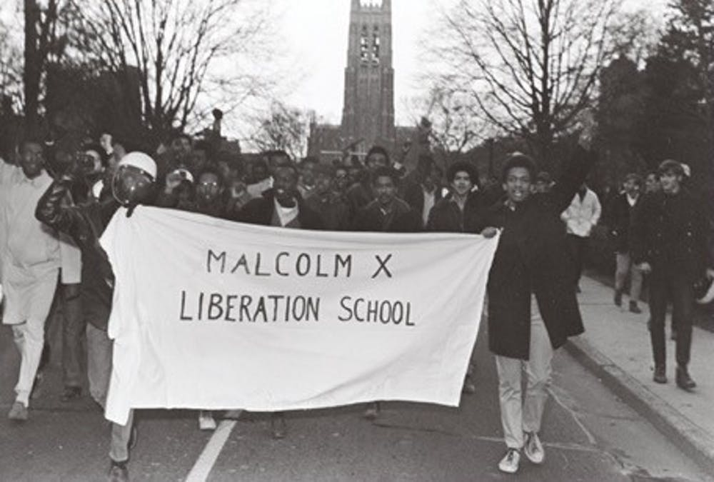 The protesters renamed the Allen Building the Malcolm X Liberation School in solidarity with protests around the country. After vacating the Allen Building, the protesters and their supporters walked down Chapel Drive. Courtesy of the Durham Civil Rights Heritage Project (The Herald Sun).