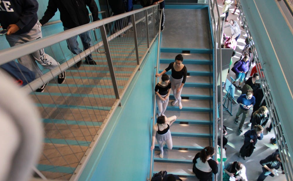 A group of dancers walks down from the second floor of the Rubenstein Arts Center.